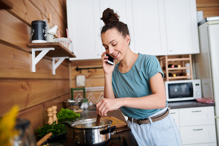Cooking and phoning Stock Photo