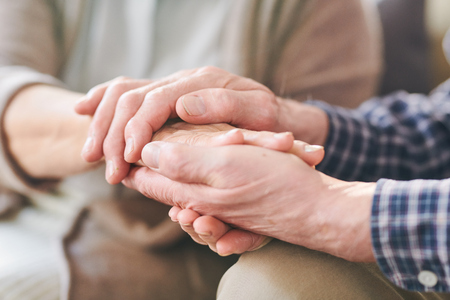 Senior man and woman holding hands of one another as symbol of togetherness, support and care Stock Photo