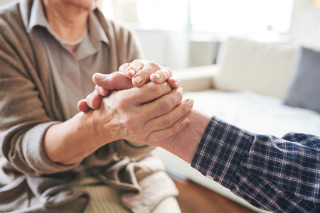 Mature retired woman holding hand of her senior spouse or caregiver expressing support, affectiona and love