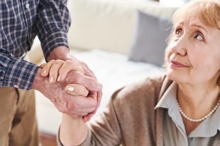 Reife kranke oder gestresste Frau, die ihre Pflegekraft oder ihren Ehemann anschaut, während sie seine helfende Hand hält Standard-Bild