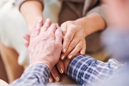 Aged spouses making pile of hands while expressing love, support and care about each other