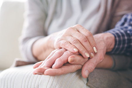 Hands of mature wife or carer holding that of her aged husband or patient as expression of care and support Foto de archivo - 121685973