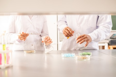 Close-up of unrecognizable agricultural scientists in lab coats standing at lab bench and making experiments with plants