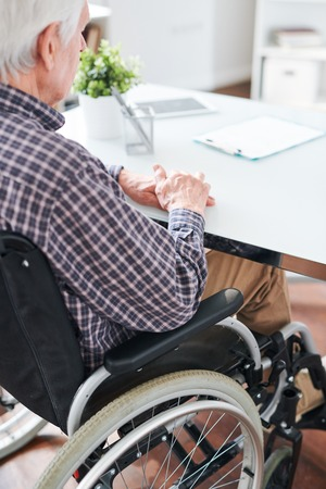 Mature lonely handicapped man in wheelchair sitting by desk in office or hospital while waiting for someone