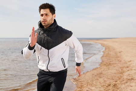 Guy jogging on the beach