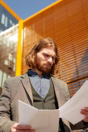 beard man reading paper