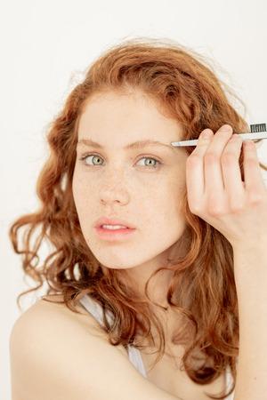 Woman brushing eyebrows Фото со стока - 122956148