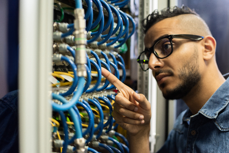 Middle-eastern network engineer checking cables