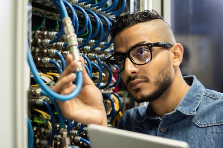 Technical engineer examining mainframe computer Stock Photo