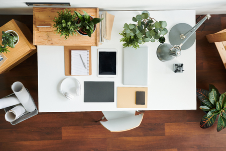 View of contemporary workplace of architect or office worker with gadgets, lamp, notebook and some green plants on desk Stockfoto