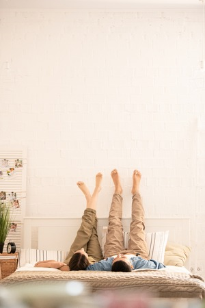 Young carefree barefoot dates in casualwear lying on bed with their raised legs opposite wall while relaxing at home Stock Photo