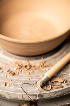 Part of wooden stick with steel working edge lying on rotating pottery wheel with clay workpiece and shavings