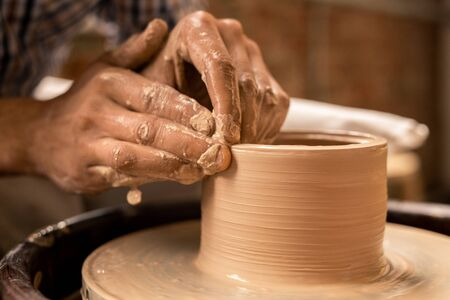 Hands of artisan holding rotating workpiece of clay pot while working by pottery wheel in his workshop