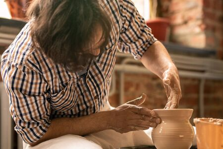 Contemporary young craftsman sitting by rotating pottery wheel while shaping raw clay pot in his workshop