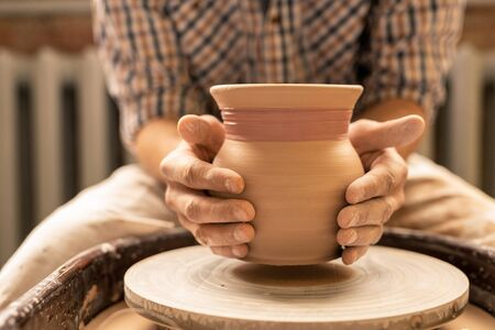 Master of pottery or young artisan holding new clay pot over wheel while working over new collection of earthenware Stockfoto