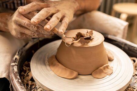 Alfarero joven que usa una herramienta de mano especial para procesar la parte inferior de un nuevo artículo de arcilla mientras se inclina sobre el torno de alfarería