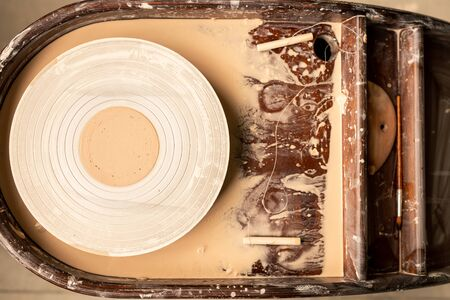 Overview of white pottery wheel with raw liquid clay on its top and paintbrush for decorative painting by workplace Stockfoto