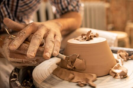 Master of pottery craft making sides of new clay bowl flat and smooth with special handtool during work