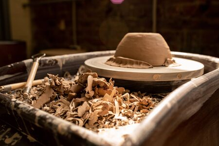 Pile of clay shavings after processing work on background of pottery wheel with new bowl in workshop of artisan