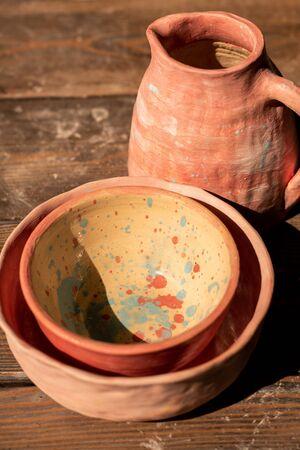 Set aus neuem Steingut bestehend aus zwei bemalten Schalen und Krug auf Holztisch gebrauchsfertig