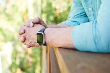 Hands of restful man with wristwatch leaning against wooden banisters while spending time in the country house at summer