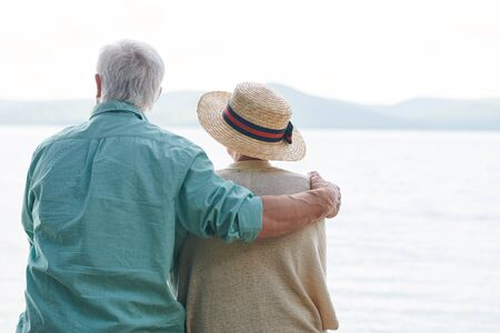 Peaceful and romantic senior couple in casualwear spending time by seaside and enjoying weather and the day Stock Photo