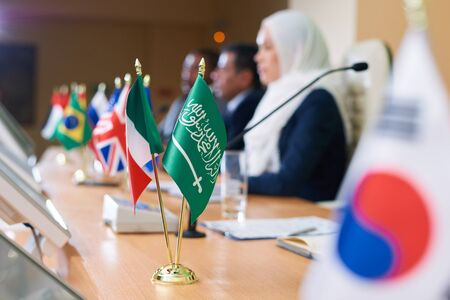 Green flag of muslim country and tricolor one on long table Фото со стока