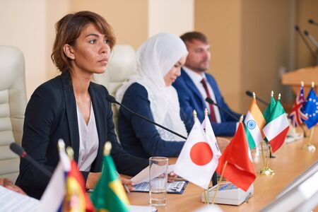 Young serious businesswoman in formalwear listening to speaker report while sitting by table on background of intercultural colleagues