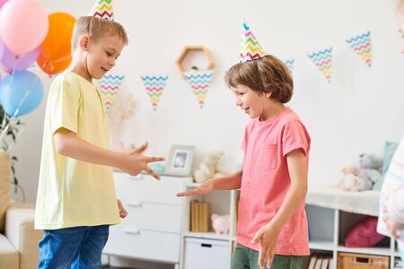 Two cute little boys in birthday caps and t-shirts playing childish game