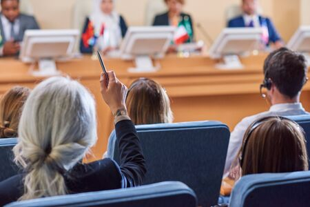 Back view of audience in armchairs raising their hands to ask questions to speaker after report at conference Stock Photo
