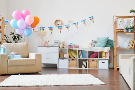 Bunch of colorful balloons and stack of giftboxes on armchair in the living-room