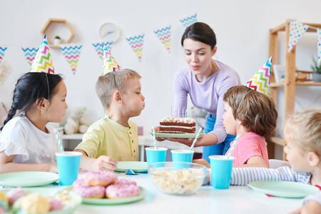Young mother helping little kids to blow candles on birthday cake Stockfoto