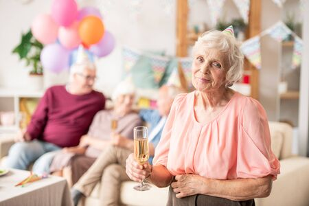 Gracious senior female with flute of champagne