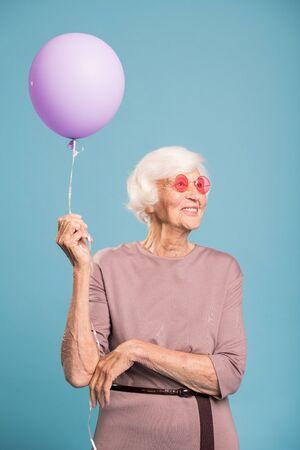 Happy senior female in elegant dress holding balloon