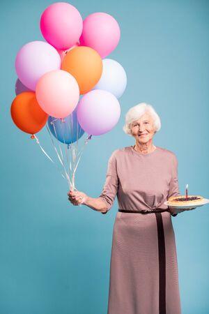 Happy aged woman in elegant dress celebrating birthday