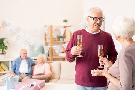 Senior spouses toasting with flutes of champagne Stock Photo