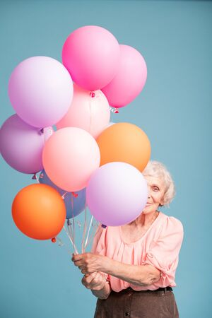 Happy senior woman peeking out of colorful balloons
