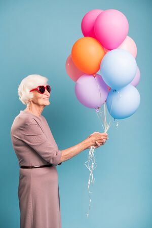 Elegant and gracious senior female holding bunch of balloons Banco de Imagens