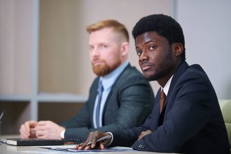 Young African businessman in suit listening to coach
