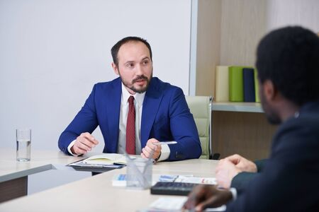 Confident businessman in formalwear consulting colleagues