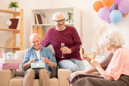 Two happy senior man and their wives enjoying home party