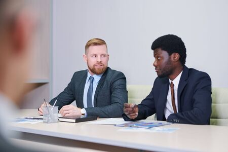Two young intercultural businessmen discussing working points
