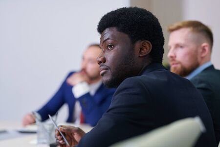 Serious young African businessman or student listening to speaker Standard-Bild