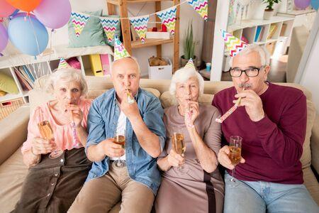 Grupo de amigos mayores o dos parejas que soplan silbatos
