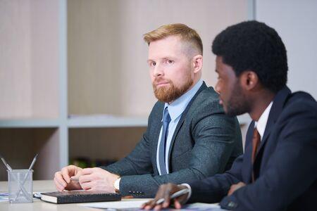 Serious young businessman listening to speaker at seminar Standard-Bild
