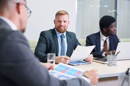 Young businessman with paper consulting with colleague