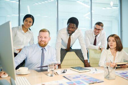 Group of intercultural brokers watching webinar or online conference