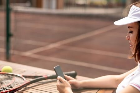 Young female tennis player messaging in her smartphone