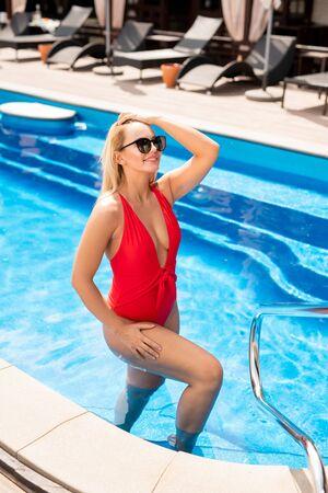 Feliz chica rubia en traje de baño rojo saliendo de la piscina Foto de archivo