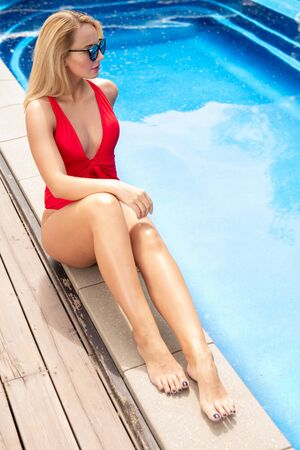 Young fit attractive female in red swimwear sitting by poolside